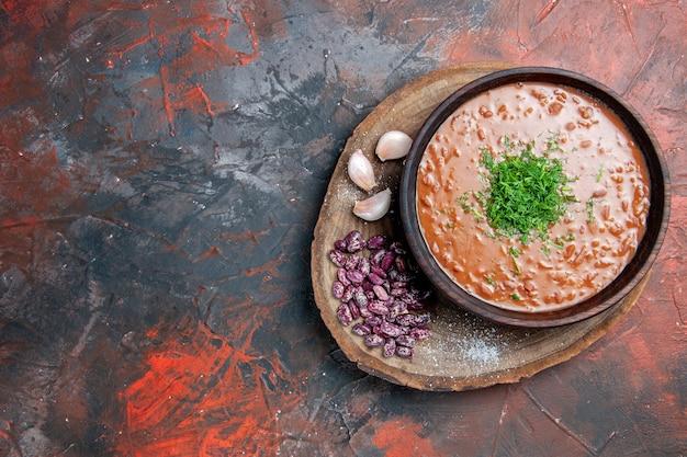 Vista superior da sopa de tomate com alho e feijão na tábua de madeira no lado direito da mesa de mistura de cores