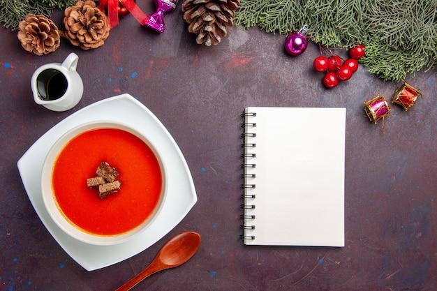 Vista superior da sopa de tomate com pão fatiado dentro em preto Foto gratuita