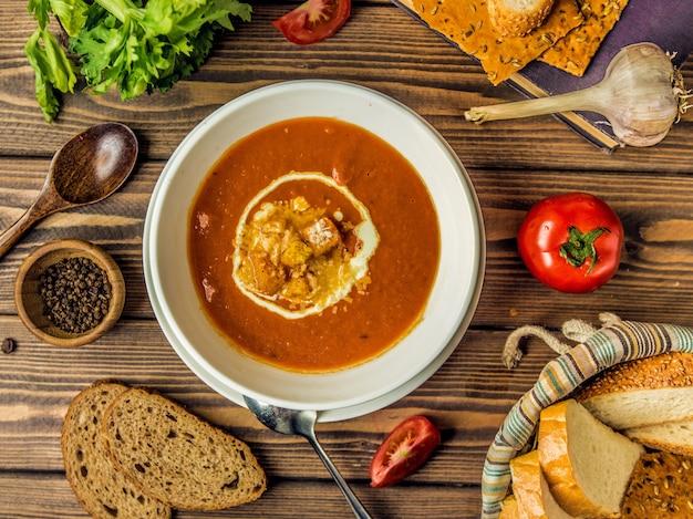 Vista superior da sopa de tomate com queijo derretido e bolacha nele