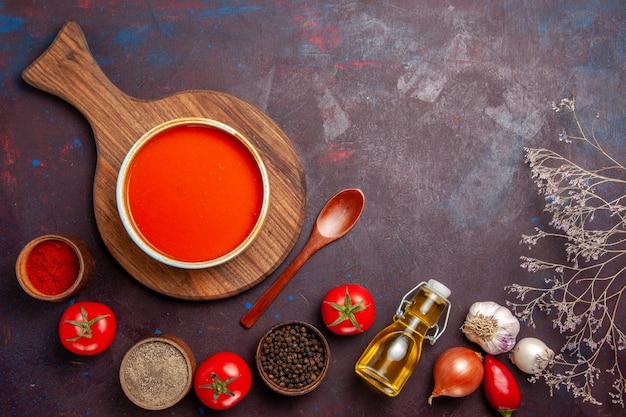 Vista superior da sopa de tomate com temperos no preto