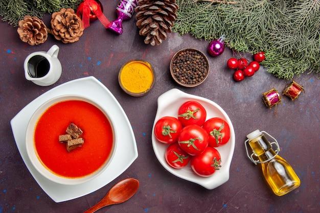 Vista superior da sopa de tomate com tomates frescos e temperos no preto
