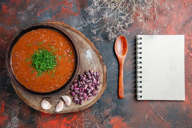Vista superior da sopa de tomate, feijão, alho na colher de corte e caderno na mistura de fundo de cor