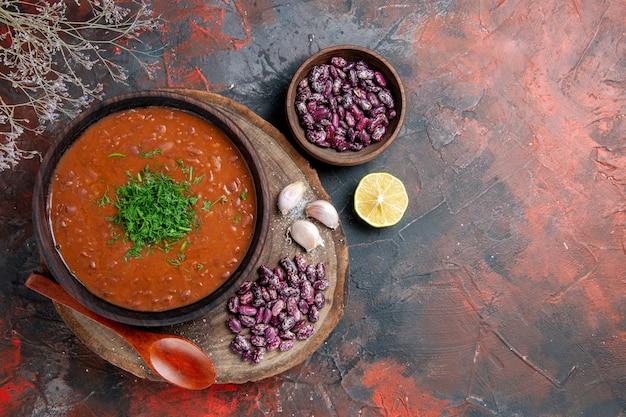 Vista superior da sopa de tomate, feijão, alho na tábua de madeira e colher na mesa de cores diferentes
