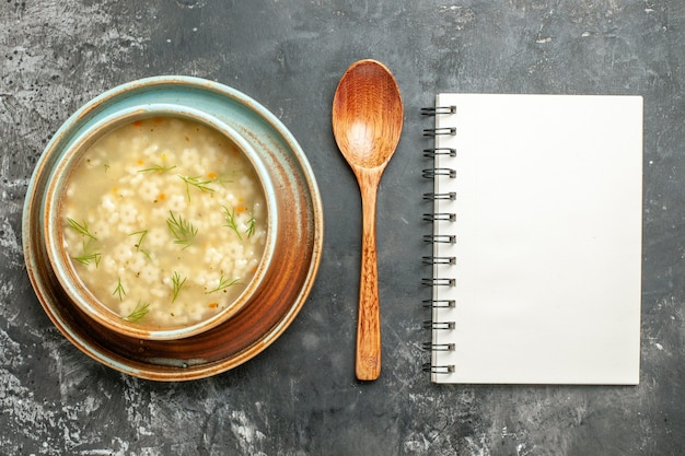 Vista superior da sopa estrela em um bloco de notas em uma tigela com colher de madeira