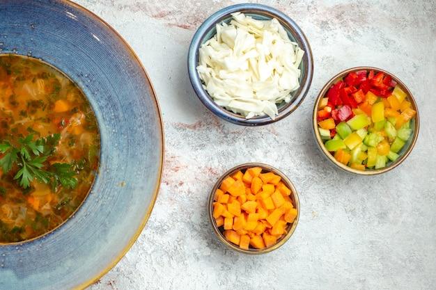 Vista superior da sopa quente de vegetais com vegetais fatiados no espaço em branco