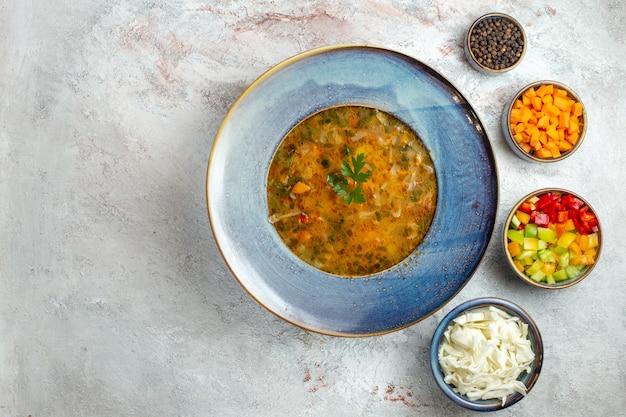 Vista superior da sopa quente de vegetais dentro do prato em um espaço branco claro