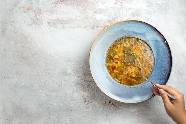Vista superior da sopa quente de vegetais dentro do prato na mesa branca