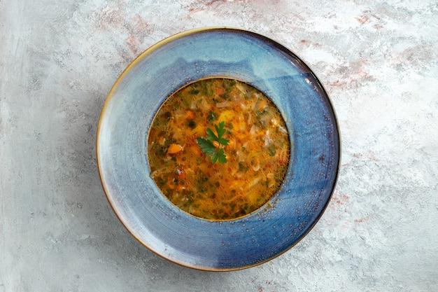 Vista superior da sopa quente de vegetais dentro do prato no espaço em branco
