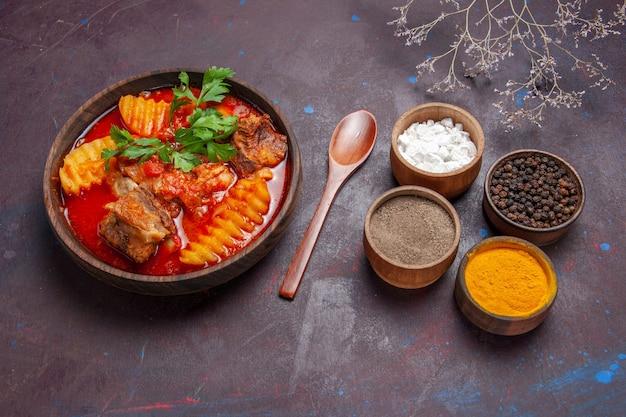 Vista superior da sopa saborosa de molho de carne com diferentes temperos no preto