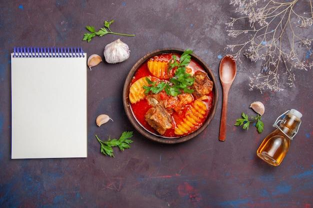 Vista superior da sopa saborosa do molho de carne com verduras e batatas fatiadas no preto