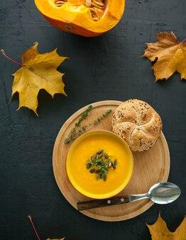 Vista superior da sopa vegana de abóbora caseira com sementes, ervas e pão