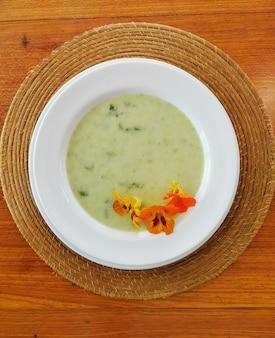Vista superior da sopa verde com flores comestíveis.