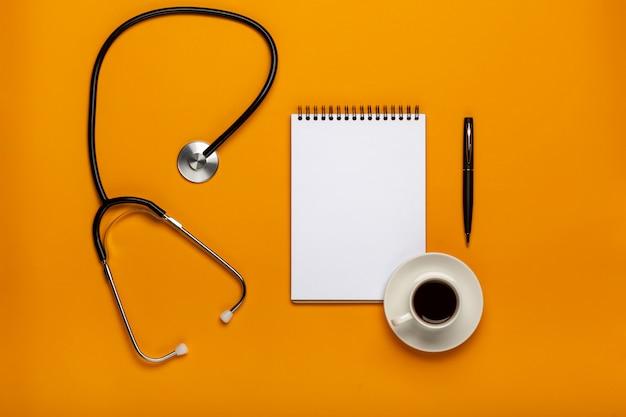 Vista superior da tabela da mesa do doutor com estetoscópio, café e papel vazio na prancheta com pena. vista superior com espaço de cópia, lay plana