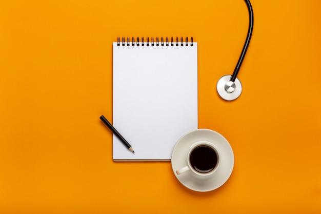 Vista superior da tabela da mesa do doutor com estetoscópio, café e papel vazio na prancheta com pena.