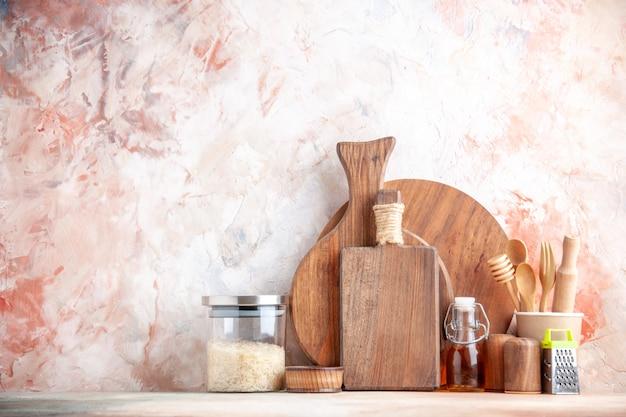 Vista superior da tábua de cortar colheres de madeira ralador kumquats com caule na panela e arroz em vidro na superfície colorida