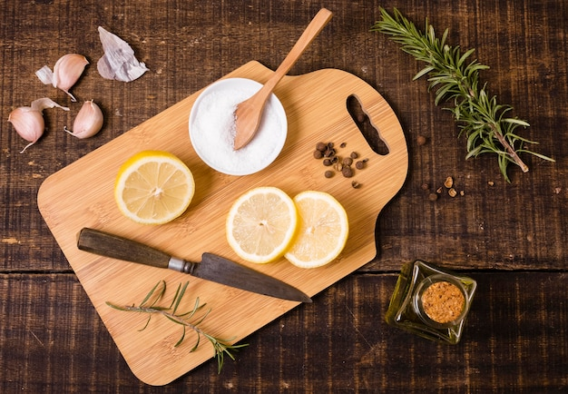 Vista superior da tábua de cortar com faca e rodelas de limão