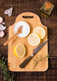 Vista superior da tábua de cortar com rodelas de limão e faca