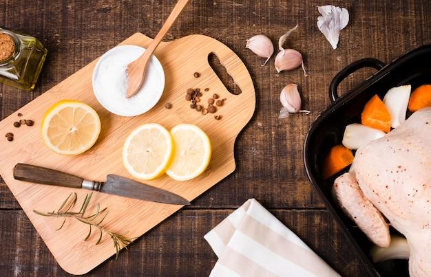Vista superior da tábua de cortar com rodelas de limão e frango