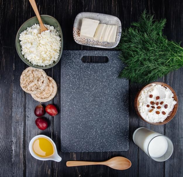 Vista superior da tábua de cozinha e queijo cottage em tigelas, bolos de arroz, um copo de leite e mel em um pires com erva-doce na mesa preta