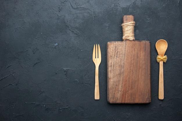 Vista superior da tábua de servir de madeira, colher de pau e garfo na mesa escura.