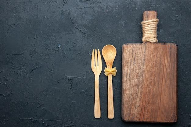 Vista superior da tábua de servir de madeira, colher de pau e garfo no espaço da cópia da mesa escura