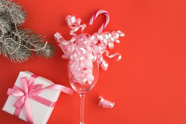 Vista superior da taça de champanhe e presente no vermelho
