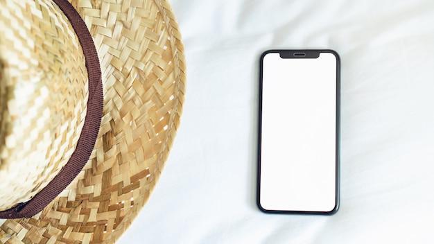 Vista superior da tela em branco do smartphone na sala e chapéu, durante o tempo de lazer.