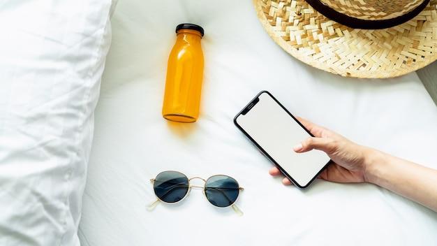 Vista superior da tela em branco do smartphone na sala e chapéu, óculos, durante o tempo de lazer.
