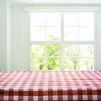 Vista superior da textura da toalha de mesa quadriculada em desfocar o fundo do jardim da vista da janela.