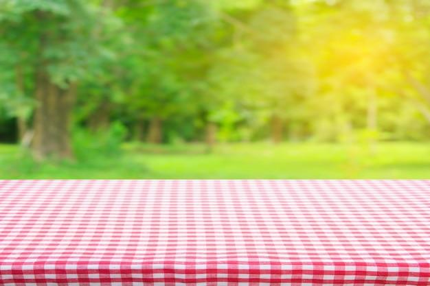 Vista superior da textura da toalha de mesa quadriculada vermelha com bokeh verde abstrato