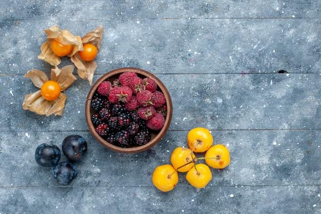 Vista superior da tigela com bagas frescas e frutas maduras em uma mesa cinza, floresta suave fresca de frutas de baga