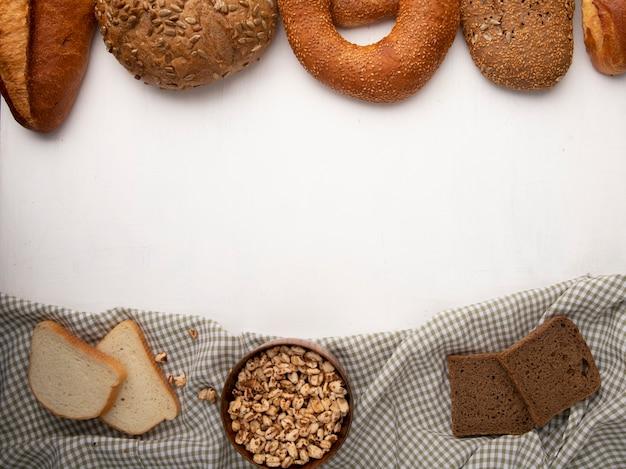 Vista superior da tigela com calos e fatias de pão branco e centeio no pano com outros pães no fundo branco, com espaço de cópia