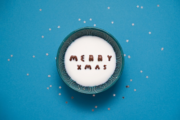 Vista superior da tigela com cereais do alfabeto de leite e chocolate. texto de feliz natal.