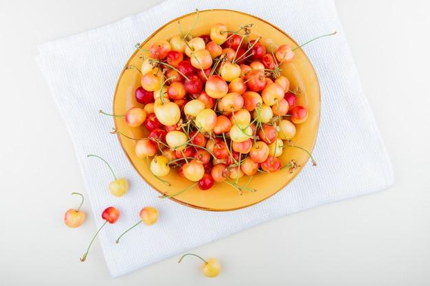 Vista superior da tigela com cerejas no pano e branco