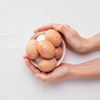 Vista superior da tigela com ovos de páscoa decorados nas mãos