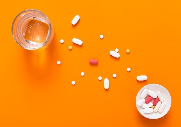 Vista superior da tigela com pílulas e copo de água