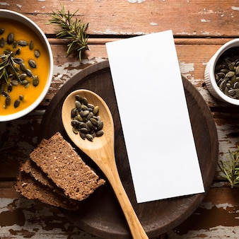 Vista superior da tigela com sopa de abóbora com sementes e colher de pau