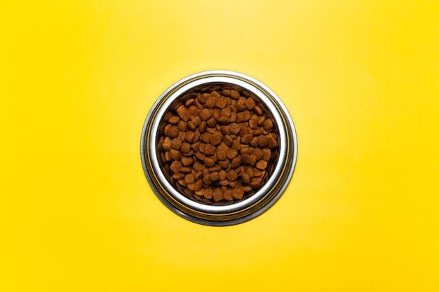 Vista superior da tigela de aço com comida seca para gatos em fundo de cor amarela.
