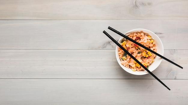 Vista superior da tigela de arroz frito chinês com pauzinhos pretos na mesa de madeira