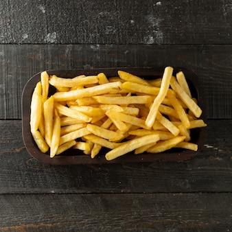 Vista superior da tigela de batatas fritas na superfície de madeira