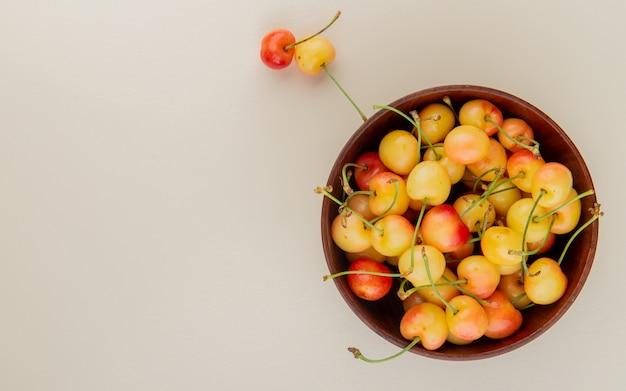 Vista superior da tigela de cerejas amarelas com cerejas no lado direito e branco com espaço de cópia