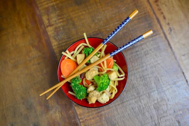 Vista superior da tigela de comida asiática de yaksoba com legumes, um palito em uma mesa rústica