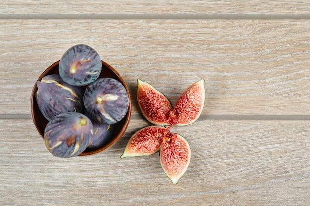 Vista superior da tigela de figos pretos e fatias de figos em uma mesa de madeira. foto de alta qualidade