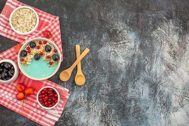 Vista superior da tigela de frutas vermelhas com colheres de cerejas de aveia e frutas coloridas na toalha de mesa