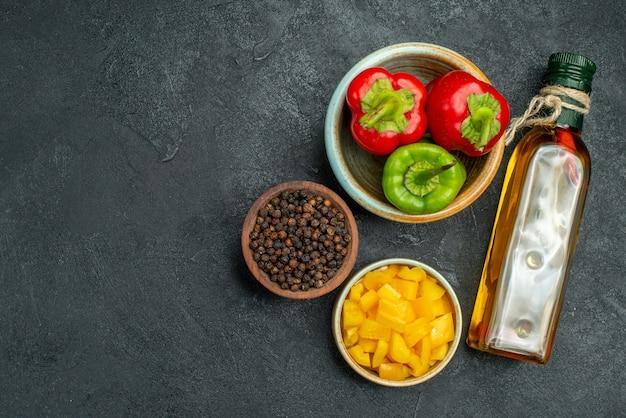 Vista superior da tigela de pimentão no lado direito com o frasco de óleo de tigelas de ervas e vegetais ao lado na mesa verde