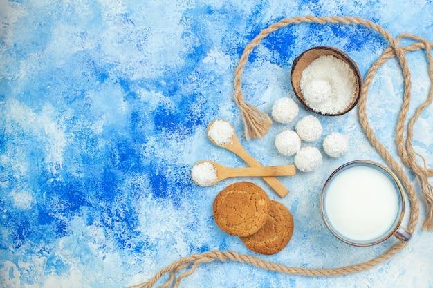 Vista superior da tigela de pó de coco e bolas de coco em fundo branco azul