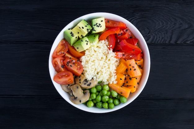 Vista superior da tigela de pokê vegan com cuscuz e vegetais
