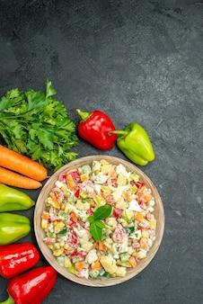 Vista superior da tigela de salada de legumes com folhas de cenoura e pimentão na mesa cinza escuro