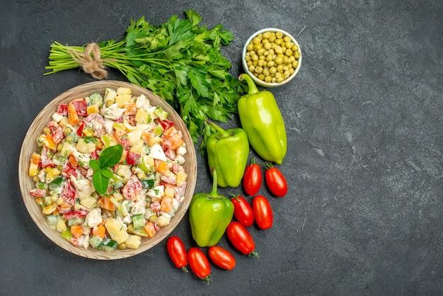 Vista superior da tigela de salada de legumes com legumes ao lado na mesa verde escura