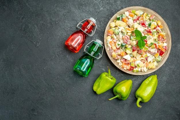 Vista superior da tigela de salada de legumes com pimentão e garrafas de óleo e vinagre na mesa verde escura